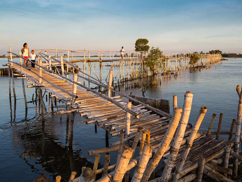"""On Foot""--One of two ways to the island: via a long precarious bamboo bridge, accessible when tides are low."
